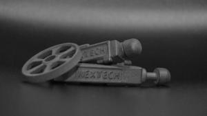 Tre grå 3D printede emner med navnet Nexttech på siden af to to