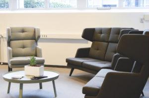 2 store og 1 grå sofa omkring et bord i kontorfællesskabet
