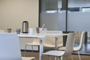 Mødelokale med hvide stole og hvide borde