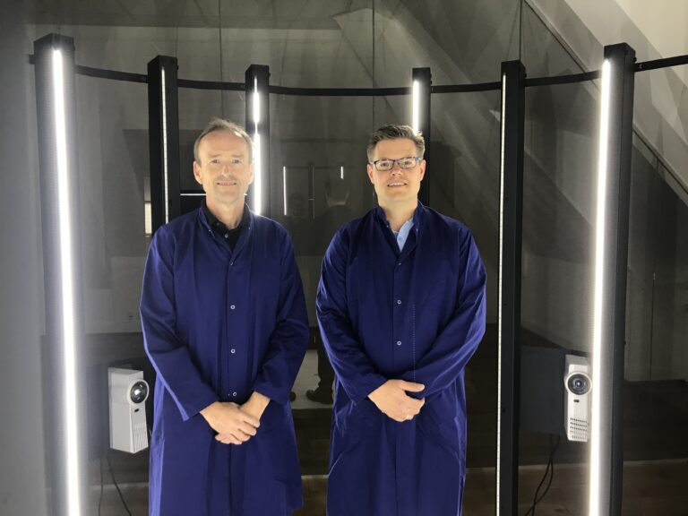 Karsten og samarbejdspartner er iklædt blå kedeldragter. De to mænd er fotograferet i det rum, hvor man scanner billeder forud for 3D print af figurer.