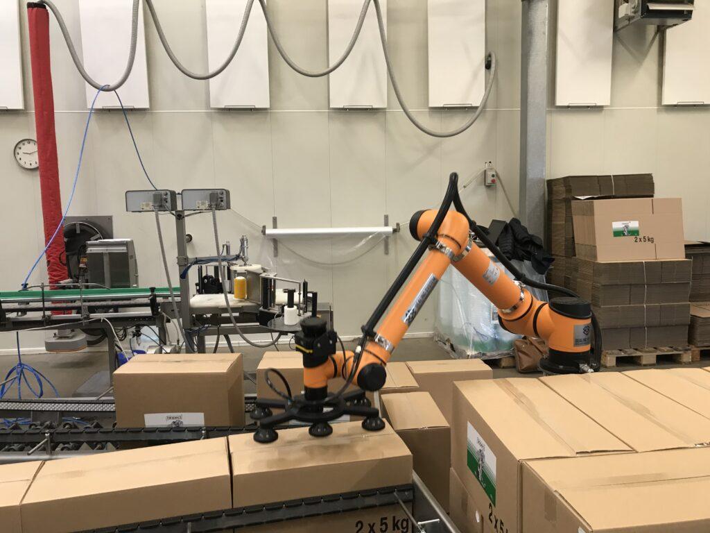 Robotværktøj samt en holder. Robotarmen er gul. Der er seks sugekopper på maskinen. I for- og baggrunden ses papkasser.