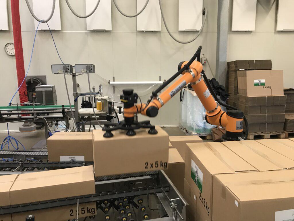 Robotværktøj samt en holder. Illustreret på pakkebord hos Sealing System. Robotarmen er gul. Der er seks sugekopper.